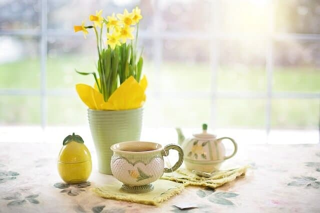 A table set with a tea cup, tea pot and daffodils