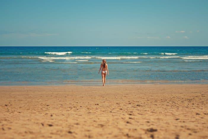 A Girl in a Swimwear Walking Towards an Isolated Beach