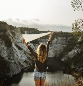 A Delighted Girl Standing in Front of the Mountains