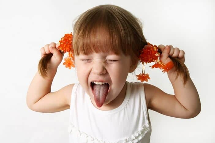 Attitude of a young girl sticking out her tongue
