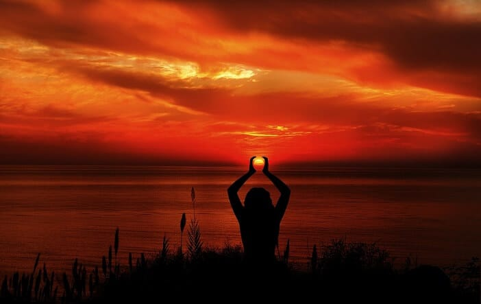 A girl meditating and empowering herself during sunset.
