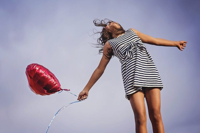 A happy girl letting go of balloon.
