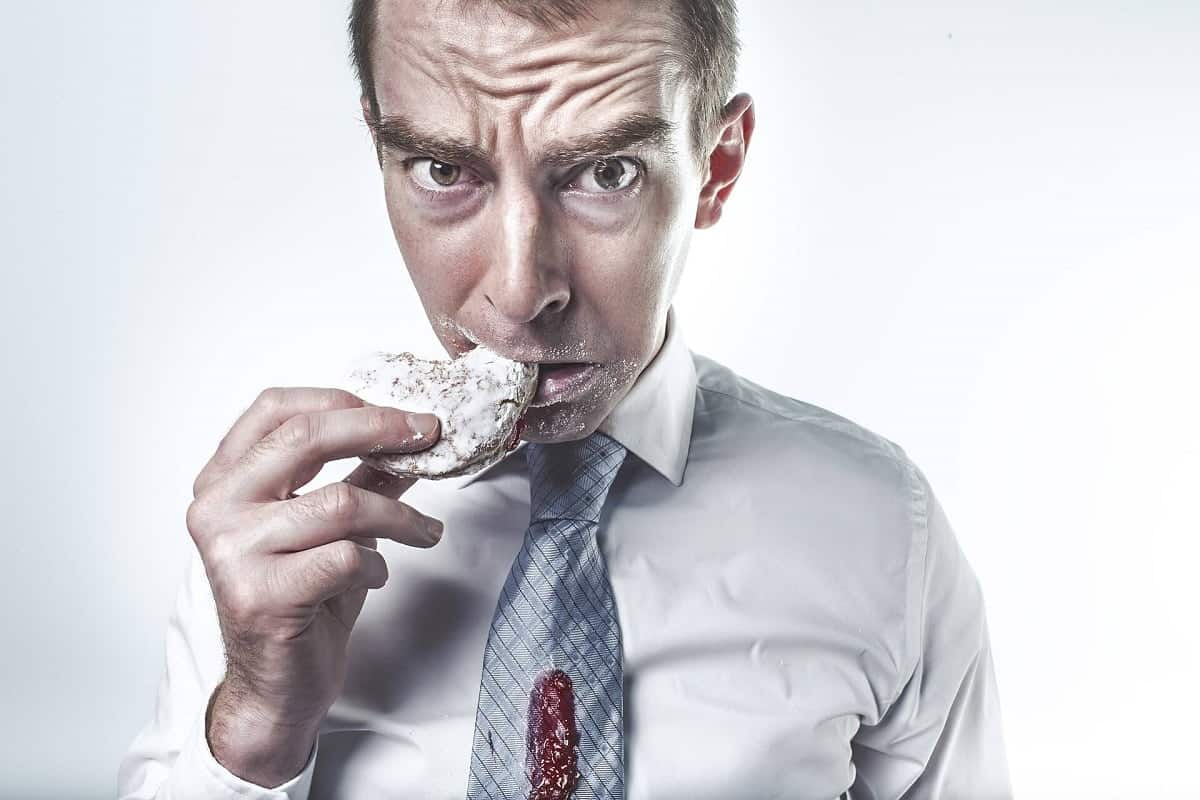 A greedy man who is dieting, eating a jam filled biscuit.