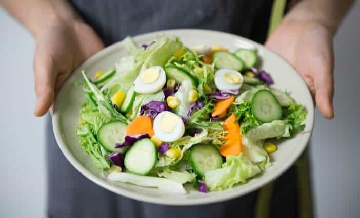 A girl holding salads on a plate- Illustration of a crash diet.