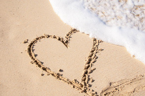 sea wave sweeping on a heart sign made on sand